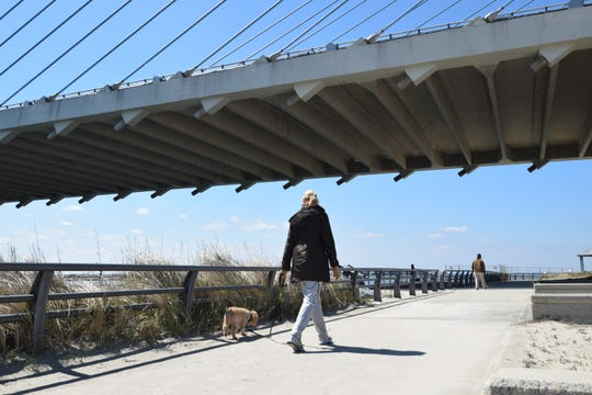 Rehoboth Beach resident Debbie Roy walks her dog Charley along the Indian River Inlet. Normally she'd walk on the beach, but most have been closed to halt the spread of the coronavirus.