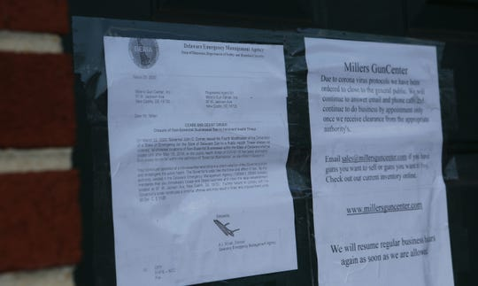 A notice on the front of Miller's Gun Center informing them to close their doors to walk in customers during the coronavirus pandemic.  The business can continue selling online and in-store by appointment only.