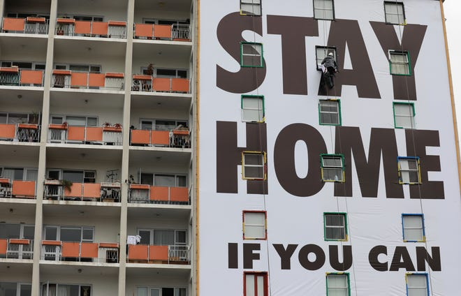A billboard is installed on an apartment building in Cape Town, South Africa, on March 25, 2020.