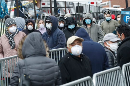 Patients wear personal protective equipment while maintaining social distancing as they wait in line for a COVID-19 test at Elmhurst Hospital Center in New York.