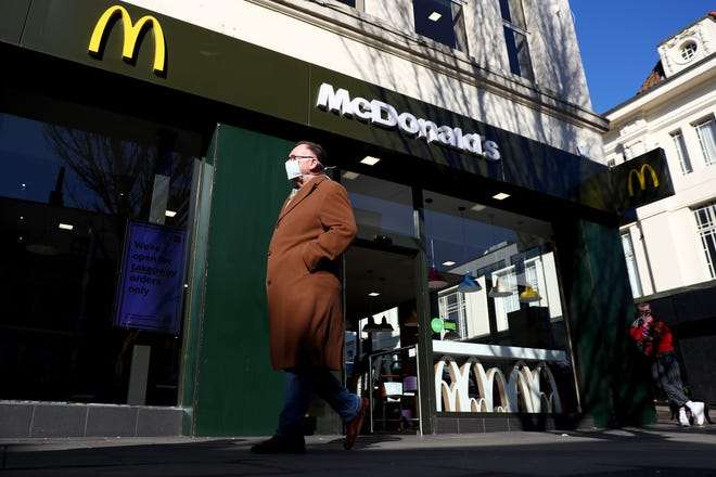 A man wearing a facemask walks past a McDonald's restaurant after the fast food chain announced that they would be closing all of their UK restaurants at the end of the day on March 23 in Brighton, United Kingdom.