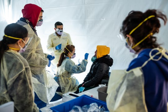 Doctors test hospital staff with flu-like symptoms for coronavirus in set-up tents to triage possible COVID-19 patients outside before they enter the main Emergency department area at St. Barnabas Hospital in the Bronx on March 24, 2020 in New York City.