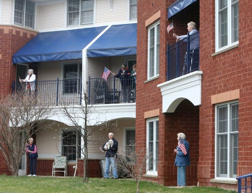 Residents at The Waterford at St. Luke Senior Independent Living Community emerge from their apartments to wave flags and sing