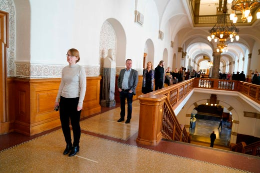 Members of the Danish Parliament stand in line to vote one by one on another emergency law to combat the coronavirus pandemic, outside the Parliament at Christiansborg Castle, Copenhagen, Denmark, on March 26, 2020.