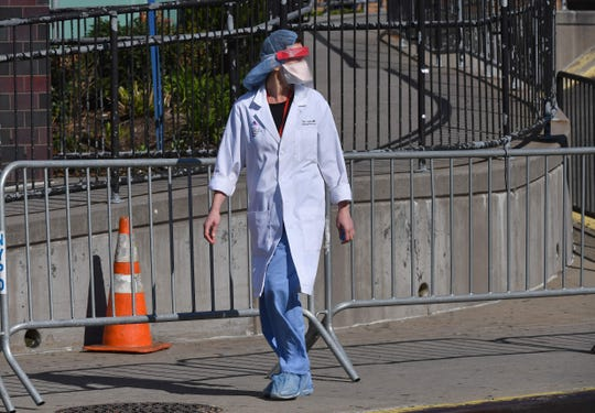 A physician outside Elmhurst Hospital Center in the Queens borough of New York City on March 26, the day after officials reported 13 COVID-19 patients had died at the hospital in a 24-hour span.