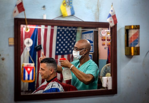 Barber Eugenio Lafargue, reflected in a mirror wearing a protective face mask against a precaution against the spread of the new coronavirus, styles a customer's hair, in Havana, Cuba, Wednesday, March 25, 2020.