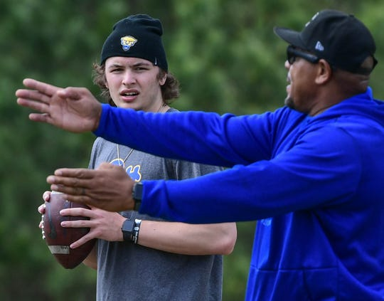 Davis Beville, left, a rising sophomore at Pitt, listens to quarterback coach Ramon Robinson, Founder and President of the South Carolina non-profit company Elite Position Training (EPT) and RR Elite QB Academy during a workout in Piedmont.