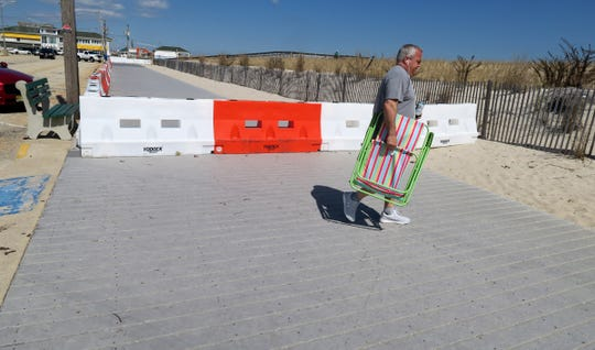 Vincent Vacante, Whiting, heads to the beach with his chair Friday afternoon, March 27, 2020, past barricades that close the boardwalk in Seaside Park.