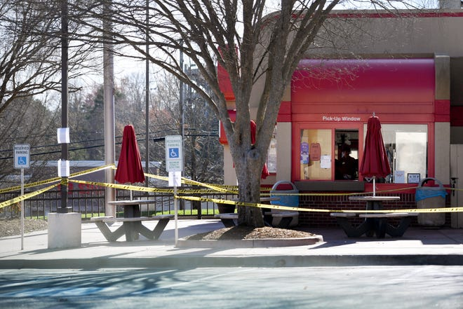 In this file photo, employees of Chick-fil-a on Tunnel Road serve customers through the drive-thru window as their outdoor dining area is wrapped in caution tape hours before the Buncombe County Stay Home, Stay Safe declaration went into effect on March 26, 2020. Chick-fil-A is replacing this store with another nearby.
