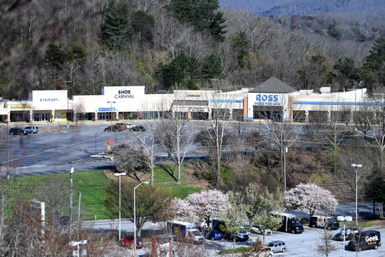 A shopping center parking lot is almost empty on Tunnel Road hours before the Buncombe County Stay Home, Stay Safe declaration went into effect on March 26, 2020. The declaration closed non-essential businesses in an effort to curb the spread of novel coronavirus.