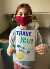 Hazel Chaltraw of Battle Creek poses for a picture with a card she made for a neighbor who donated milk to her family while they are in a self-imposed quarantine.