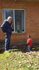 Cutsinger's son-in-law Dave Murphy and his great-grandson visit Arlene Cutsinger outside her window.