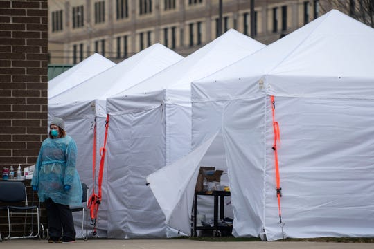 Temporary triage tents are set up for COVID-19 screenings outside Grace Health in downtown Battle Creek, Mich. on Wednesday, March 18, 2020.