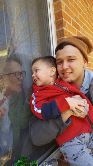 Arlene Cutsinger visits with her great-grandson Charlie Murphy and his son Chase.
