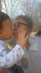 Arlene Cutsinger kisses her great-great grandson Axton through the window.