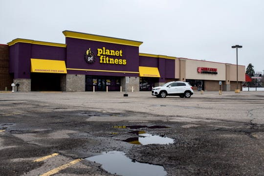 "A single car is parked at Planet Fitness in Battle Creek, Mich. on Friday, March 27, 2020 during the ""stay home"" order to slow the spread of COVID-19."