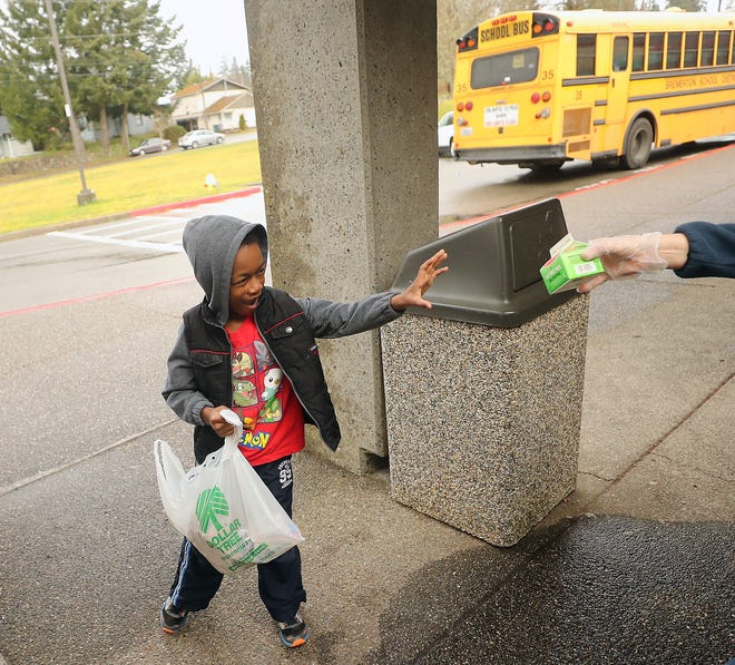 Phillip Hardy Jr., 6, happily accepts a carton of milk from Jessi Carson, kitchen lead at West Hills STEM Academy, on Friday. School districts have been using buses to deliver meals daily to school sites and bus stops along selected routes.