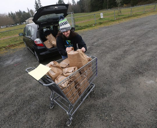 West Hills STEM Academy counselor Kasia Roque loads weekend meals packaged by the Bremerton Backpack Brigade into her car for distribution at the school on Friday, March 27, 2020.