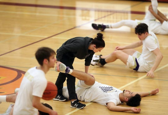 North Kitsap athletic trainer Julie Leslie stretches out Shaa Humphrey prior to the start of their regional game against Tumwater at Mount Tahoma High School in Tacoma on Saturday, Feb. 29, 2020.