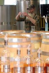 Head distiller Kevin Barrans mixes up a batch of hand sanitizer at Bainbridge Organic Distillers on Thursday, March 26, 2020.