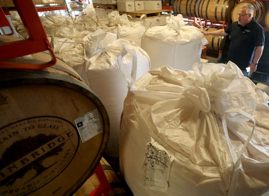 Keith Barnes stands among the bags containing 26,000 pounds of donated corn they have started processing into hand sanitizer at his Bainbridge Organic Distillers.
