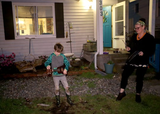 Quinn Knutelsky, 8, pauses to tune up his ukelele as he and mom Jessica, bang pots and pans and cheer in the front yard of their Bremerton home to show appreciation for health care workers on Thursday.