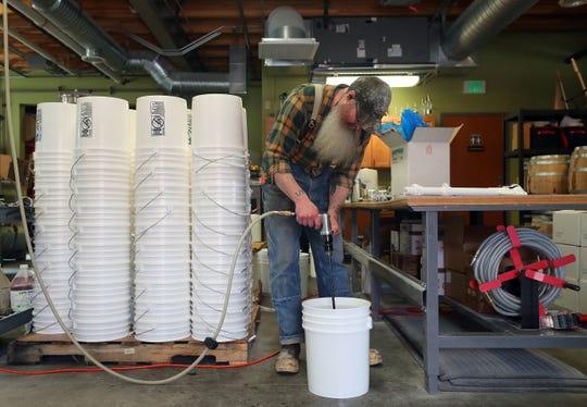 Head distiller Kevin Barrans uses a power mixer to make a large bucket of hand sanitizer at Bainbridge Organic Distillers.