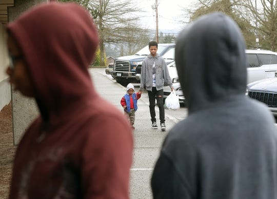 Jamari Hardy, 15, walks little brother William, 2, down the sidewalk after the family picked up meals at West Hills STEM Academy on Friday.