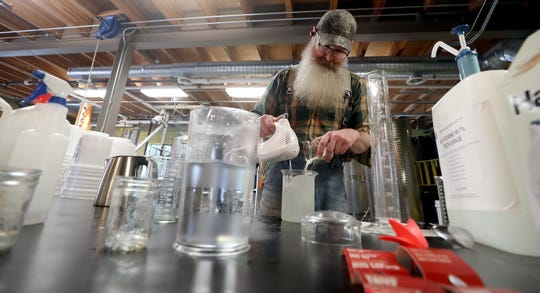 Head distiller Kevin Barrans mixes up a batch of hand sanitizer at Bainbridge Organic Distillers on Thursday. The distillery is making hand sanitizer to supply first responders, hospitals and is even providing small bottles to give away for personal use at grocery stores.