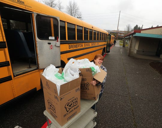 Teacher Katrina Jones laughs with coworkers as she loads meals onto a bus at West Hills STEM Academy on Friday.