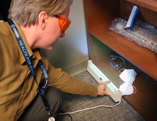 Dr. Richard St Cyr, a physician with Swedish Bainbridge Island Primary Care, turns on the UV light that he keeps on the bottom shelf of a bookcase with his PPE goggles and masks in his office on Thursday, March 26, 2020.