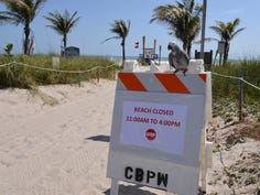 The scene at the beach at the end of Minutemen Causeway in Cocoa Beach at noon March 27, 2020. Nobody was on the beach, just a few Cocoa Beach police officers near the ramp to the beach.