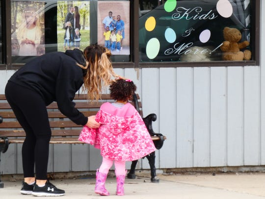 Brandy Seigneur points out the bear in her business' front window on North Sandusky Avenue to her daughter, Jaelle, Thursday afternoon. They were preparing to go bear-hunting.