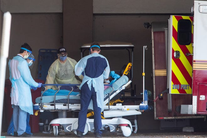 Corpus Christi Fire Department personnel, wearing protective equipment, bring a patient into Corpus Christi Medical Center-Doctors Regional emergency room Friday.