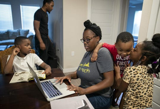 Amber Fowler, a teacher at Brooke Elementary School in Austin, tries to log in to her school portal to do some work Wednesday, while sharing space with her husband, Jacolby Scott, and their children, Javon Scott, 7, Jacolby Scott Jr., 2, and Jamiyah Scott, 5, at their apartment in South Austin. The family is stuck at home under the city's stay-at-home order due to the coronavirus pandemic.