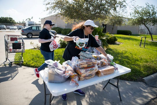 Coastal Bend Food Bank employees Sylvia Phipps, left, and Cynthia Carrillo place food on a table for three households that arrived in one car to pick up food at the on Friday, March 27, 2020. The food bank has changed it's process to a drive-thru process for the safety of volunteers, staff and those it is helping.