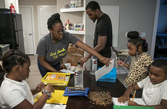 Amber Fowler, a teacher at Brooke Elementary School in Austin, and her husband Jacolby Scott, hand out lessons to their children, Jaliyah Scott, 8, from left, Jamiyah Scott, 5, and Javon Scott, 7, at their apartment in South Austin on Wednesday.