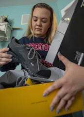 Shelby Deibler, 18, of Burlington Township, a senior at Moorestown Friends School, looks over the new hiking boots she was going to wear on the Grand Canyon school trip, Thursday, March 26, 2020.