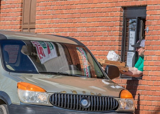 A Cristy's Pizza worker hands a customer their order as cars circle the drive through parking lot. Cristy's, like other restaurants, has been made car out only due to an order from Governor DeWine to close eateries where large groups can gather due to the coronavirus outbreak.
