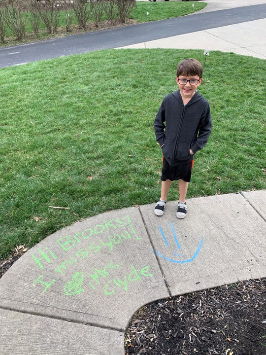Brooks Fishburn, 6, received a message on the sidewalk in front of his house from his kindergarten teacher on Tuesday, March 24, 2020, as schools across the country have moved to remote learning because of the novel coronavirus pandemic.