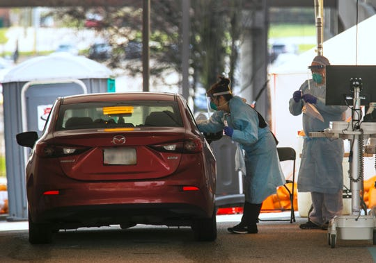 A drive-thru testing site is set up outside UC Health on Burnet Avenue near the intersection of Martin Luther King Jr. Drive, Friday, March 27, 2020. The new coronavirus pandemic has changed the way people are being tested for COVID-19. You still need a doctor's order and appointment to be tested. The license plate has been blurred to protest privacy.