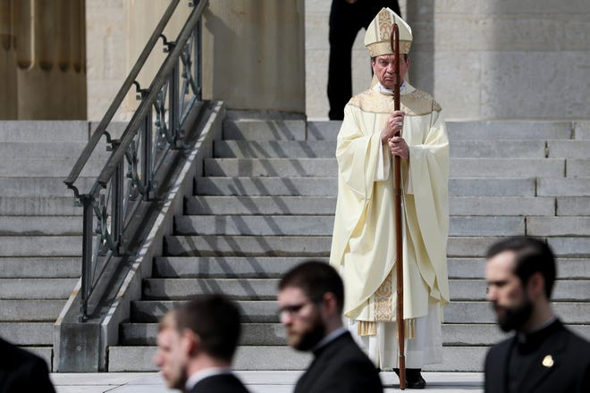 Archbishop Dennis Schnurr looks on as former Archbishop Daniel Pilarczyk's body is carried out following a Mass of Christian Burial service, Friday, March 27, 2020, at St. Peter in Chains Cathedral in Cincinnati. Daniel E. Pilarczyk, Archbishop Emeritus of Cincinnati from 1982 to 2009, died Sunday March 22, 2020. There were two people seated in the cathedral's pews and seven clergy members in attendance, said a worker with Gilligan Funeral Homes.