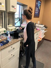 Teller Samantha Douglas of Century National bank mans the drive-thru tubes. Staff members are cleaning tubes between customers and allowing people to keep pens or cleaning those if sent back.