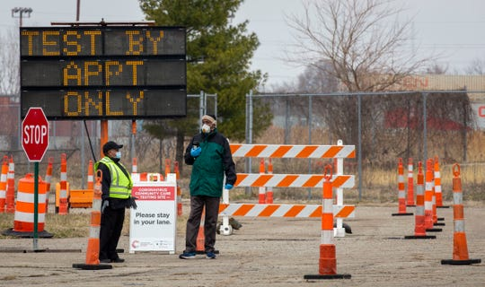 Security personnel waits for the first group of appointments at the entrance gate to the fairgrounds as the first day of testing at the COVID-19 testing facility at the Michigan State Fairgrounds in Detroit begins March 27, 2020.