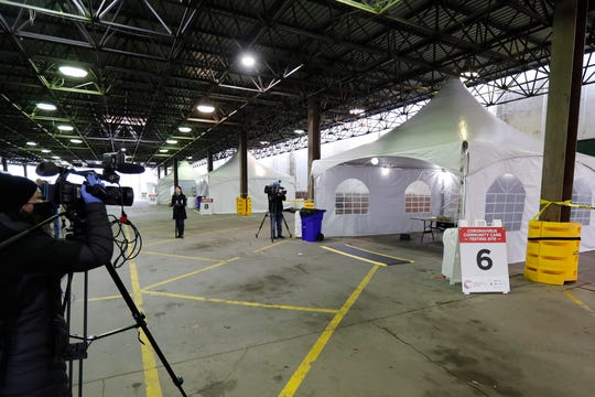Journalists photograph the examination tents at the Michigan State Fairgrounds, Friday, March 27, 2020, in Detroit, where the city is preparing for coronavirus drive up testing.