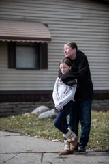 Anna Patterson and her daughter Isabella, 10, pose for a photo in front of their home in Clinton Township, Friday, March 27, 2020.