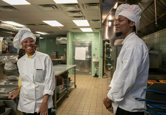 """Culinary students Dominque Collins, 29, of Troy, left, and fellow student John Laura, 34, of Detroit, volunteered to prepare meals at the commercial kitchen in the Horatio Williams Foundation building in Detroit on March 24, 2020, as part of """"Too Many Cooks in the Kitchen for Good"""""""