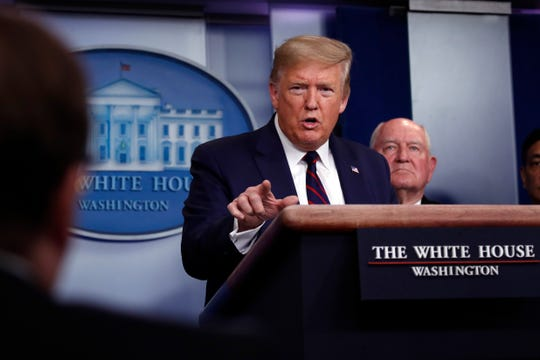President Donald Trump speaks about the coronavirus in the James Brady Press Briefing Room, Friday, March 27, 2020, in Washington as Agriculture Secretary Sonny Perdue listens.