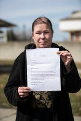 Anna Patterson shows the letter from Rivers Edge Management to notify residents to continue paying their rent of their homes in Clinton Township, Friday, March 27, 2020.