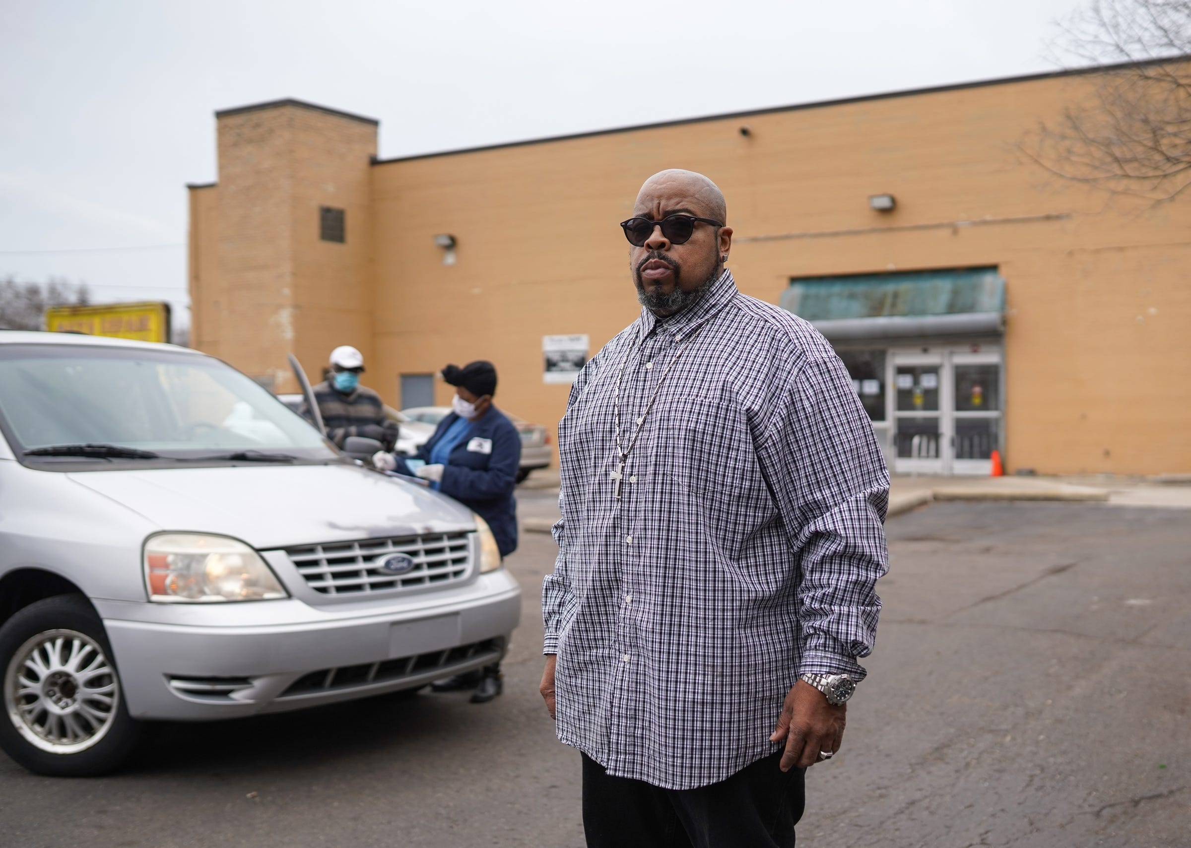 Focus : HOPE Eastside manager Tommie Felton stands outside as community members stop by to pick up food during a food pantry at the organization on Thursday, March 26, 2020 on Detroit's east side.
